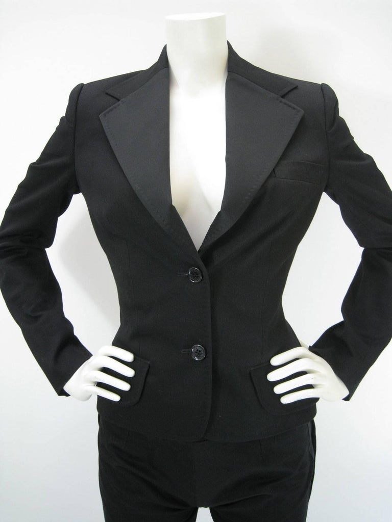 Dolce & Gabbana black satin trim pantsuit.  Tuxedo style jacket and slacks.  Jacket is fitted and has satin lapel.  Two button closure, chest pocket & faux front pockets.  Pants feature wrap around cummerbund with buckle, sailor style buttons and