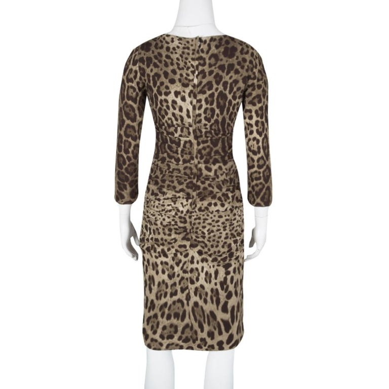 Give yourself an extremely chic look in a party by adorning this Dolce and Gabbana body-hugging knee length dress. It is artfully crafted in an animal print and has a ruched pattern to give you the freedom of moving around easily. This one-piece