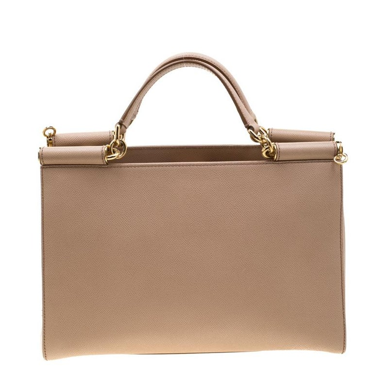 Whether it is a casual evening or a night out with your friends, Miss Sicily bag is a splendid pick for any occasion. This bag from the house of Dolce & Gabbana is crafted from beige leather and has a structured design that comes with dual top