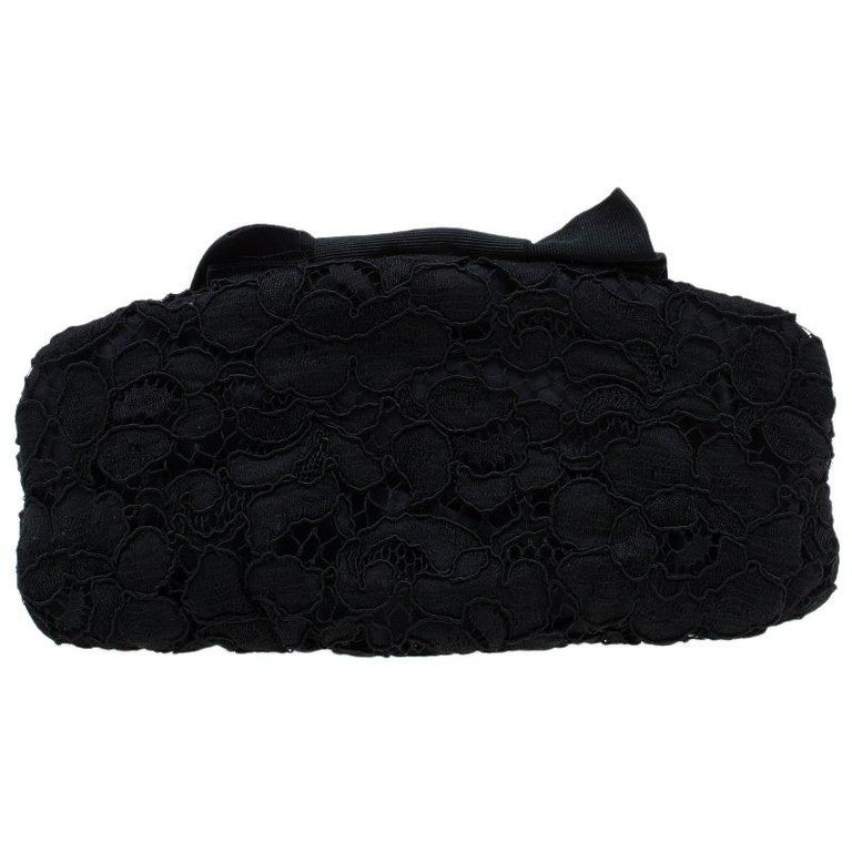 This luxurious and opulent Evening bag from Dolce and Gabbana will give your look a stylish finish. Crafted from fabric, it features an adorable lace pattern and is adorned with an impressive bow. The gorgeous black satin lined interior carries an