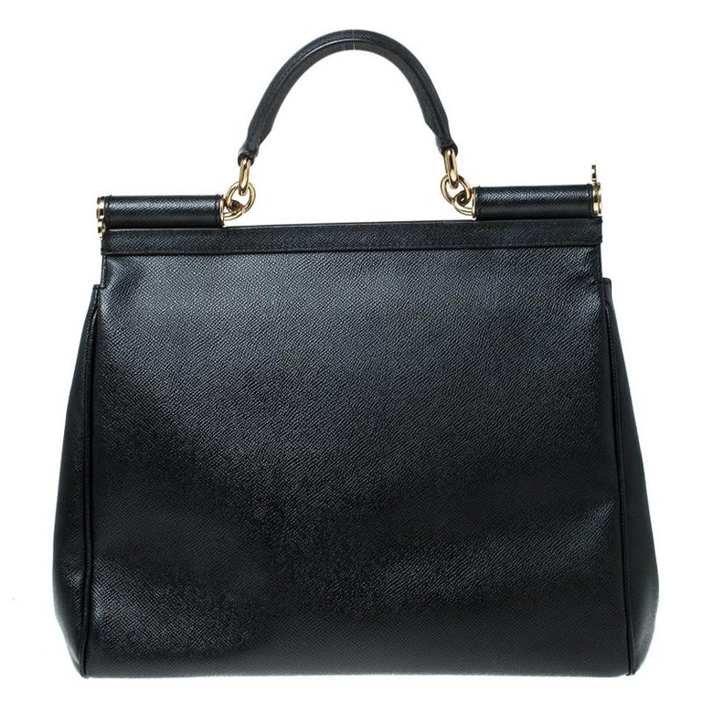 This gorgeous black Miss Sicily satchel from Dolce & Gabbana is a handbag coveted by women around the world. It has a well-structured design and a flap that opens to a compartment with fabric lining and enough space to fit your essentials. The bag