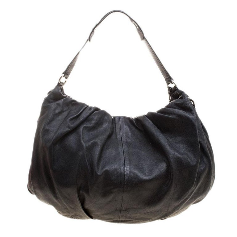 Perfect to store all that you need for the day, this Dolce and Gabbana Miss Night and Day hobo is a must have everyday essential. Crafted in black leather, this bag features pleated details on the surface along with a short and a long strap for your