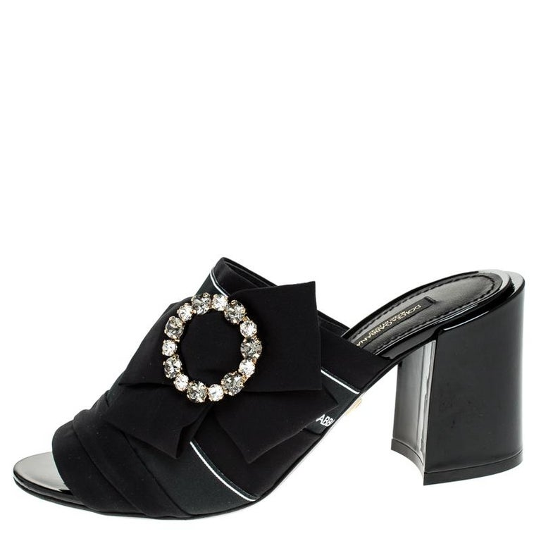 This gorgeous pair of mules by Dolce & Gabbana is made of satin and adds a classic touch to your look. They come in a classic shade of black and have an open toe silhouette. They feature a bow on the vamps that are adorned with crystal
