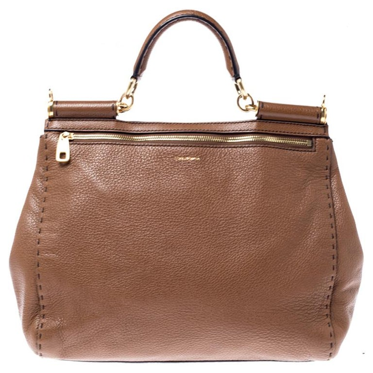 This gorgeous brown Miss Sicily bag from Dolce & Gabbana is a handbag coveted by women around the world. It has a well-structured design and a flap that opens to a compartment with leather lining and enough space to fit your essentials. The bag