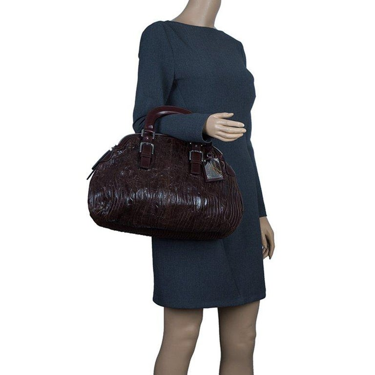 This Miss Bauletto Dome Satchel by Dolce and Gabbana is reminiscent of the vintage doctor's bag. Made from pleated leather, the exterior features double top handles, a brand logo plaque and a top zipped closure. The fabric lined interior houses