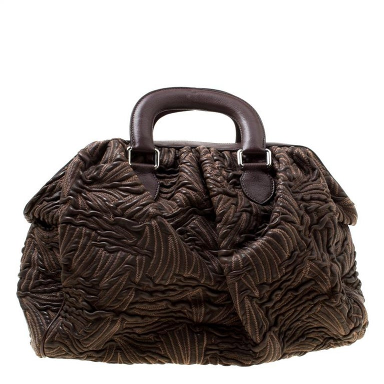 This Miss Curly bag by Dolce & Gabbana is a piece all fashionistas must look out for! Meticulously crafted from textured leather, it features a brown shade and leopard-printed kiss lock pockets. The bag is equipped with a spacious fabric interior