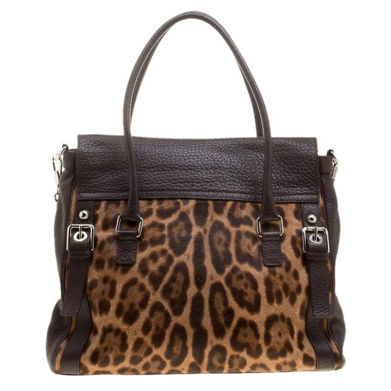 This Dolce&Gabbana bag is not only visually magnificent but also functional. It has been crafted from dark brown leather, leopard-printed calf hair and styled into a shape that is classy and posh. The bag has two top handles and a flap that reveals
