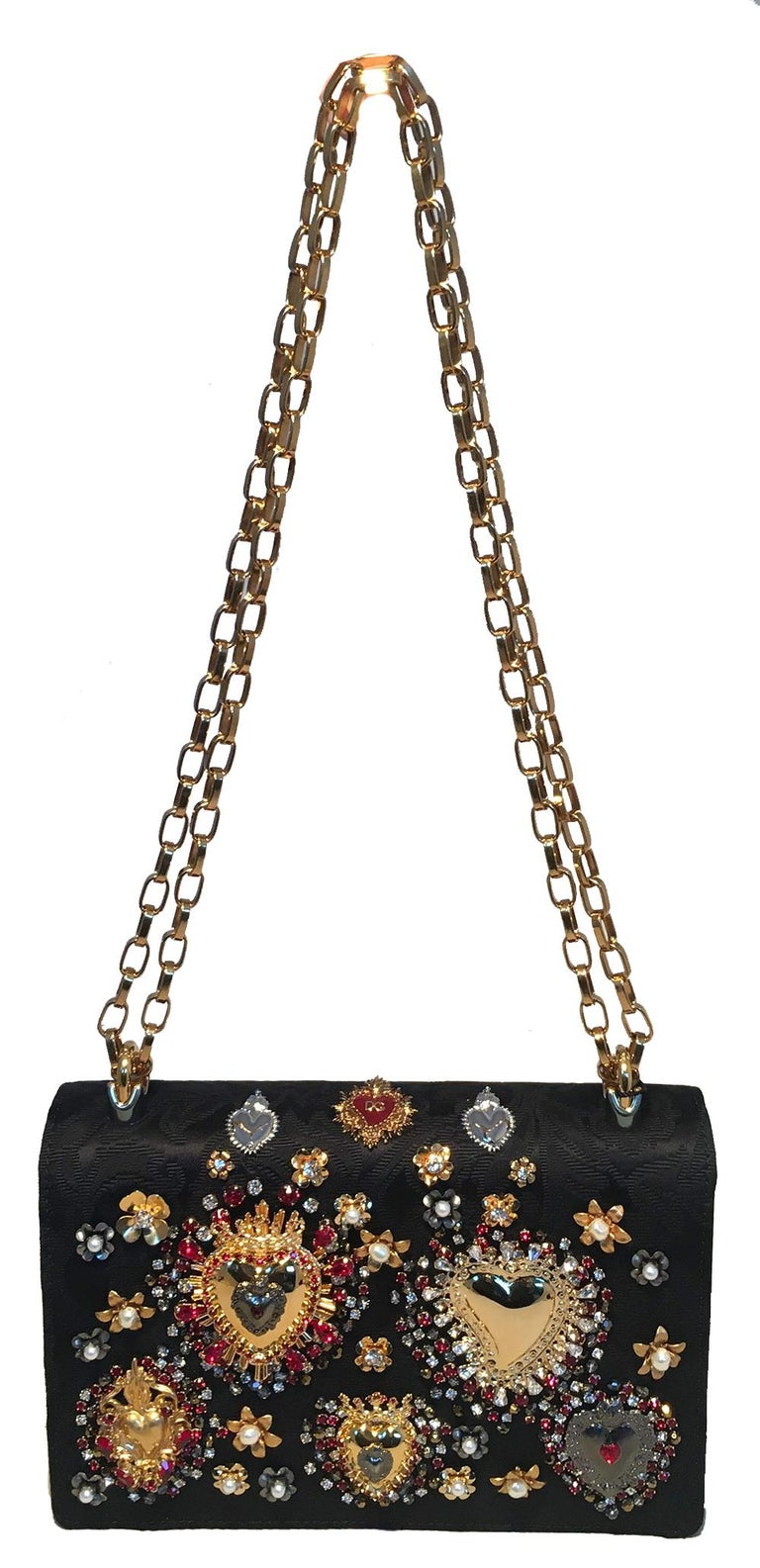 Dolce and Gabbana DG Girls Brocade Hearts Embellished Handbag NWOT condition. Black silk brocade body embellished with gold and silver metal hearts, red, grey and clear varying sized rhinestones and gold and silver metal mini flower appliques with