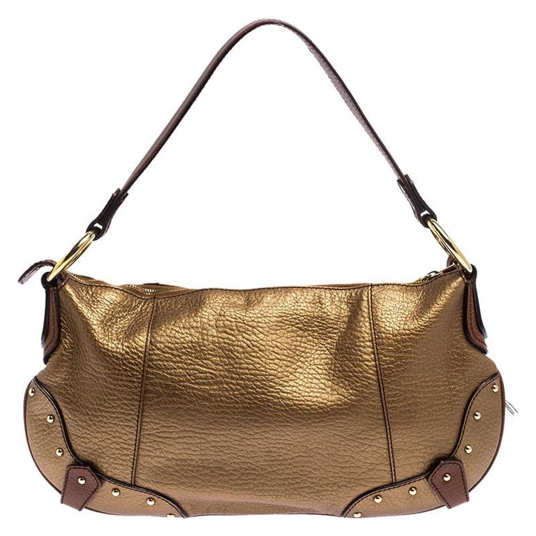 Complement the diva in you by adorning this bag from Dolce and Gabbana. Crafted from gold leather, this chic bag has an interior that is beautifully stitched with fabric for perfection. You can carry it using the single handle.  Includes: The Luxury