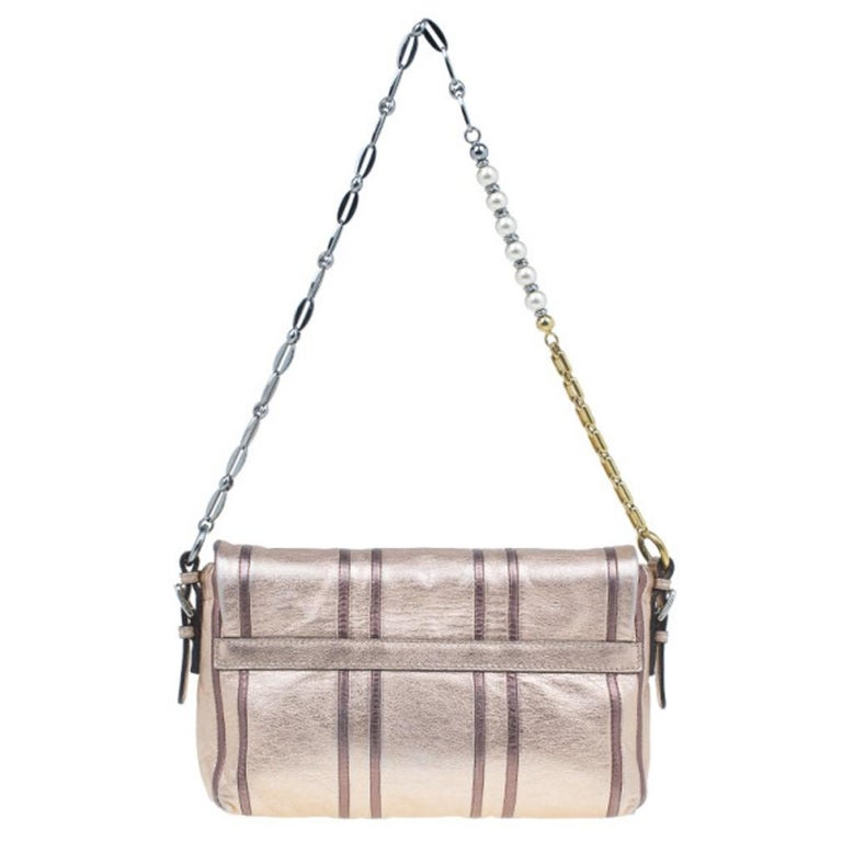 This shimmering shoulder bag by Dolce and Gabbana is a lovely handbag to own. The exterior is made from calf skin metallic pink leather with brown highlights. It is finished with a front Dolce and Gabbana plaque and showcases a chain link strap that