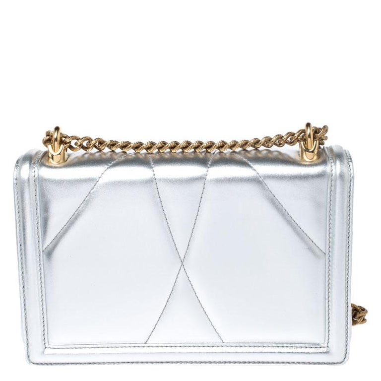 Step out in style by adorning this bag from Dolce&Gabbana. It has been crafted from silver leather and flaunts the Devotion heart motif in gold-tone on the front. It features a well-designed leather-lined interior housing a pocket. The bag is