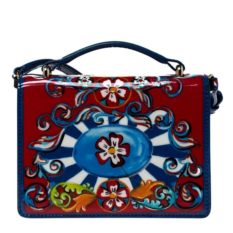 Dolce & Gabbana brings us this gorgeous Rosalia bag that has been crafted from printed patent leather and designed with a twist lock on the flap that secures a suede interior. The piece is complete with a shoulder strap and will enhance all your