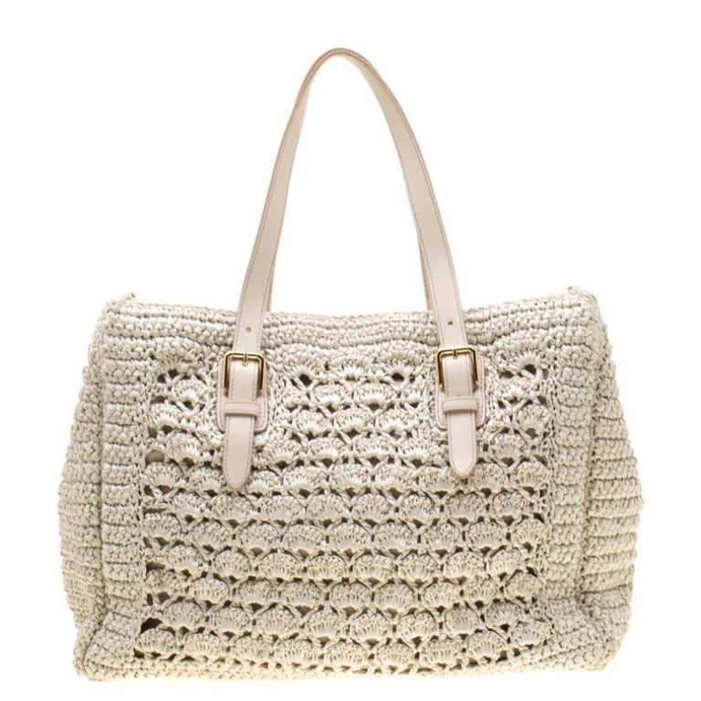 This Alma tote from the house of Dolce & Gabbana is designed in off-white Raffia crochet and comes with metal studs on the leather base. It features two top handles, a fabric-lined interior and the metal logo plaque on the front. This well-sized