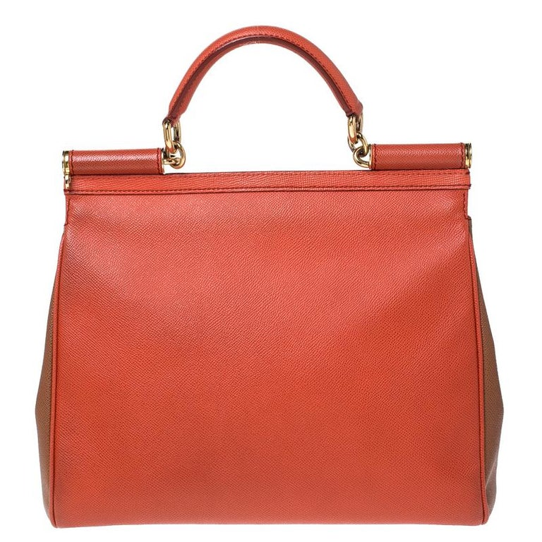 This gorgeous orange Miss Sicily satchel from Dolce & Gabbana is a handbag coveted by women around the world. It has a well-structured design and a flap that opens to a compartment with fabric lining and enough space to fit your essentials. The bag