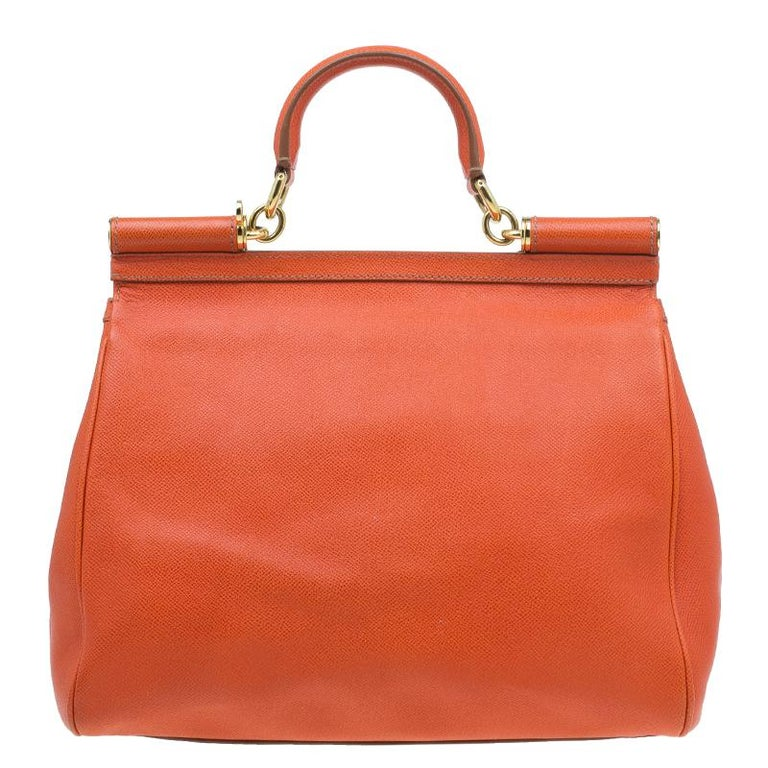 Part of the Miss Sicily collection, this Dolce and Gabbana tote is the perfect everyday bag. Crafted with textured orange leather, it comes accented with gold-tone hardware. With a structured top, it has a sturdy top handle, a flap opening with a