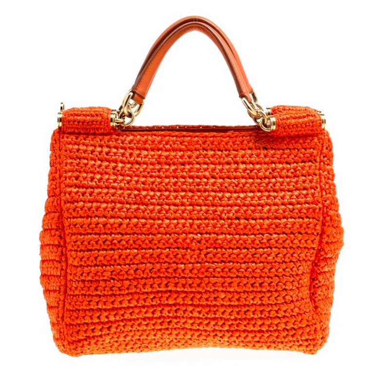 Beautiful with intricate details, this orange Miss Sicily bag by Dolce & Gabbana will get you through all seasons. The exterior is made from woven raffia and the bag features two handles and a spacious fabric interior.  Includes: The Luxury Closet