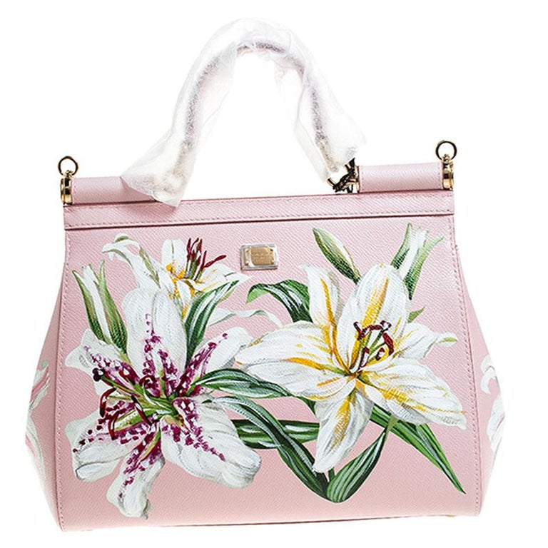 This gorgeous Miss Sicily satchel from Dolce & Gabbana is a handbag coveted by women around the world. It flaunts a pink Lilium print throughout. It has a well-structured design and a flap that opens to a compartment with fabric lining and enough