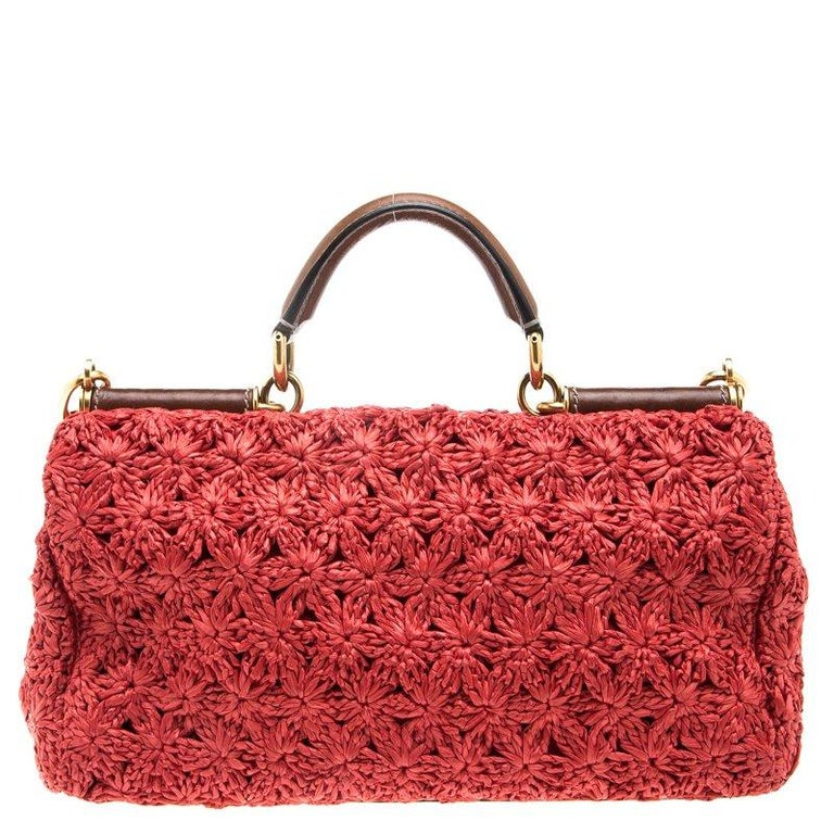 This beautiful red colored Miss Sicily bag from Dolce and Gabbana has a structured design. The bag features a woven raffia design all over. It has a top handle and an adjustable detachable shoulder strap. The front flap opens to a Leopard print
