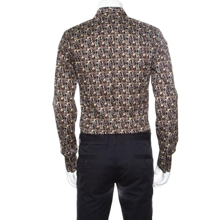 This Sicilia brown shirt from Dolce and Gabbana is the perfect shirt you've been searching for and quite worthy of being yours. It is made of a cotton blend and features a key rinted pattern all over it. It flaunts a collared neckline, front button