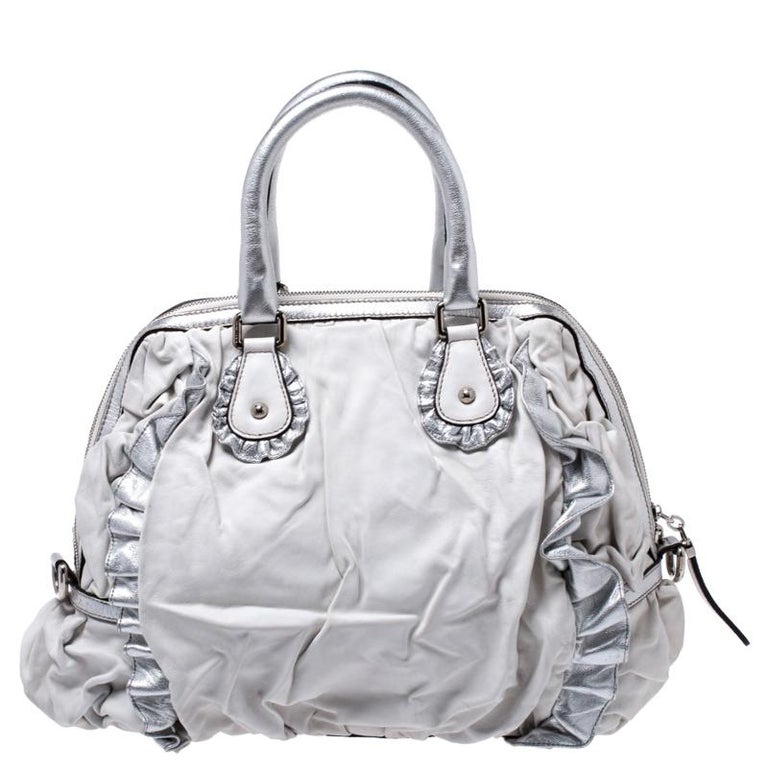 This highly functional and stylish Miss Rouche bag from Dolce and Gabbana is one to take with you when you need to carry your entire world with you. Crafted in silver leather with ruffle details, this bag features silver-tone hardware. It comes with