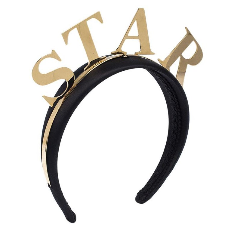 This Dolce&Gabbana headband brings a fun style. It is wrapped in black satin and detailed with gold-tone metal and the word 'STAR'. So, spread style wherever you go with this cute headband.  Includes: Original Box, Price Tag