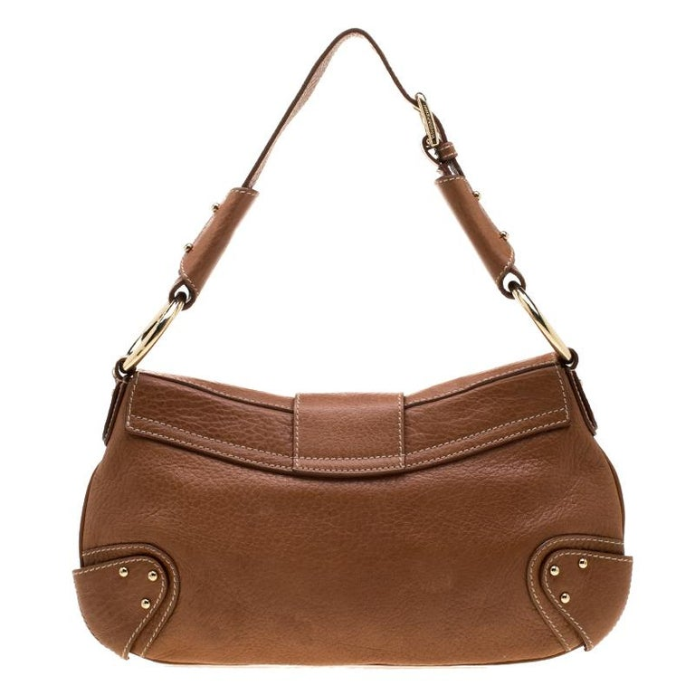 Well-made and reliable, this hobo is from Dolce and Gabbana. It has been crafted from leather and enhanced with a D-ring on the front flap. The bag is equipped with a well-sized fabric interior, a shoulder handle, and gold-tone hardware.  Includes: