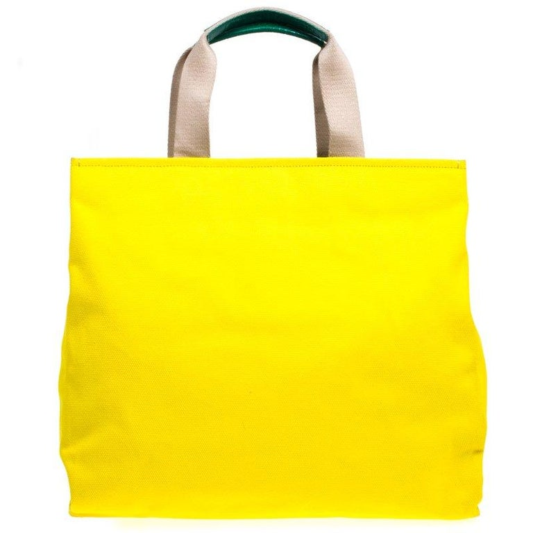 This adorable Maria shopper tote from Dolce and Gabbana is made from yellow canvas. The bright bag has a cute family patch on the front and dual top handles. The buttoned closure opens to a satin lined polka dot print interior. Shop in style with