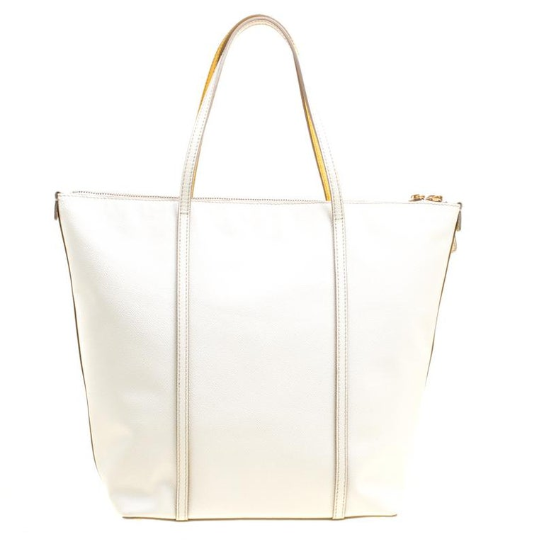 How fabulously designed is this Miss Escape tote from Dolce and Gabbana! Vibrant yellow on one side and pristine off-white on the other, this tote is crafted from leather and features a chic silhouette. It flaunts a double zip top closure, dual top