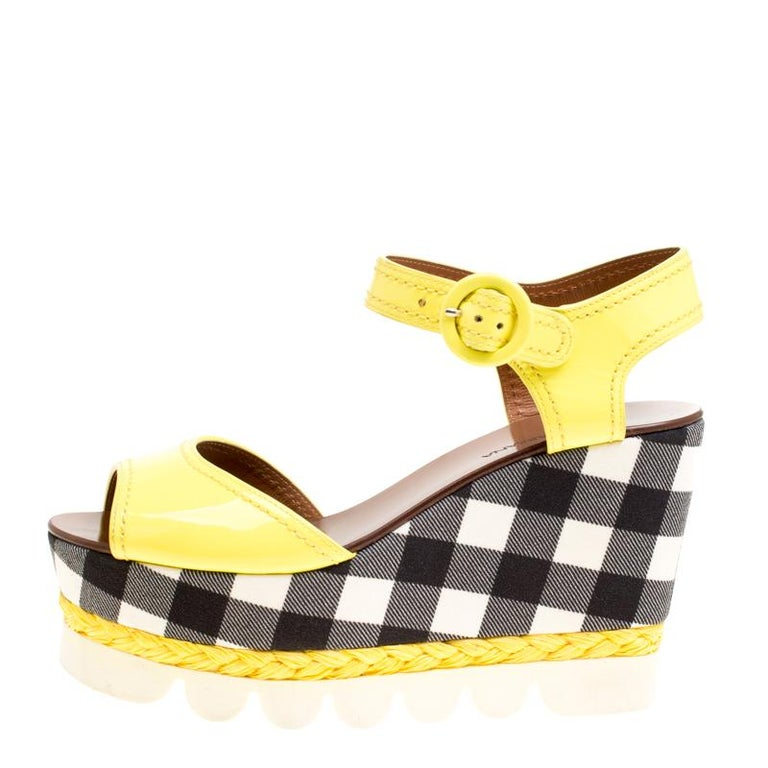 Constructed in yellow patent leather, these Dolce and Gabbana wedge sandals give subtle hints of fun style to your look. Featuring monochrome checked pattern on the platforms and wedges, these shoes are complete with matching yellow espadrille
