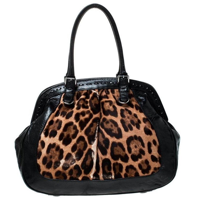 Gorgeously designed, the Miss Romantique Satchel from Dolce and Gabbana comes crafted from leopard printed calf hair and leather and features dual top handles with silver-tone buckles. It has a top closure that opens to a spacious canvas-lined