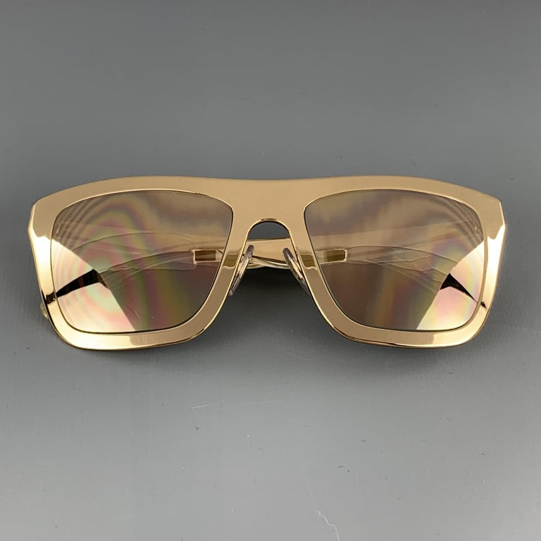 DOLCE & GABBANA sunglasses come in 18 karat gold plated polished metal in an oversized wayfarer shape with mirrored lenses and clear acrylic encased metal arms. Includes case. Made in Italy.  Very Good Pre-Owned Condition. Marked: GOLD PLATED
