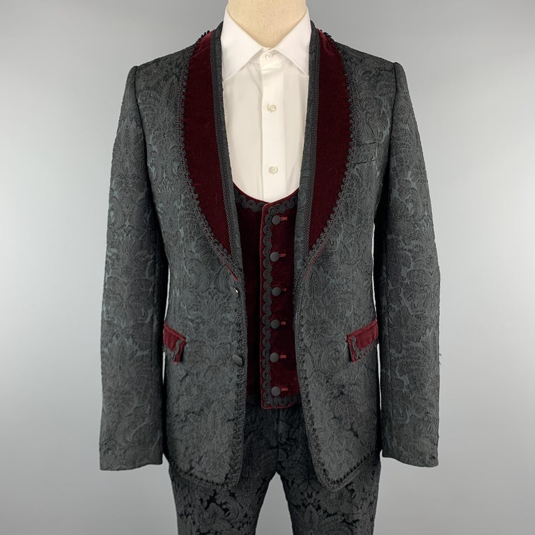 DOLCE & GABBANA three piece suit comes in black brocade fabric and includes a single breasted, two button dinner jacket with a burgundy velvet shawl collar, double vented back, and lace trim with a matching velvet vest and slim cut trousers. Made in