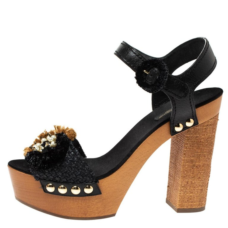 Flaunt your love for fashion and luxury with these stunning sandals by Dolce & Gabbana. Crafted in Italy, they are made from black leather and brown raffia. They are styled with open toes, vamps detailed with embellishments, buckled ankle straps,
