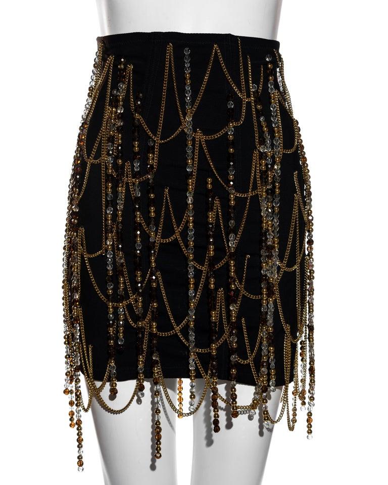 ▪ Dolce & Gabbana black corseted mini skirt  ▪ Gold metal chain detail  ▪ Beaded tassels  ▪ Metal hook closures at centre-back  ▪ IT 42 - FR 38 - UK 10 - US 6 ▪ Spring-Summer 1991