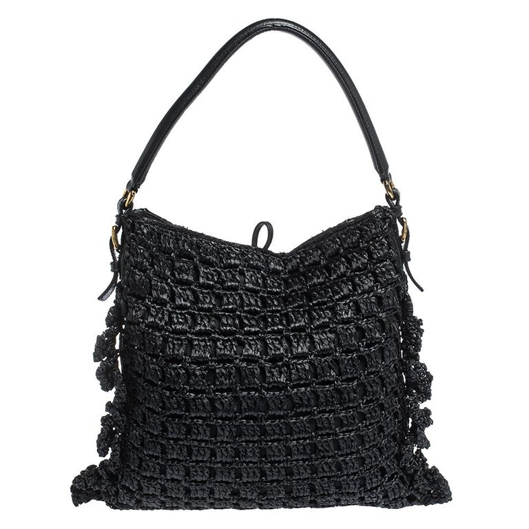 This stunning hobo by Dolce & Gabbana is a must-have. It is crafted in Italy and made of quality straw. It comes in a stunning shade of black and adds a touch of style to every outfit. The exterior features leather trims and signature brand logo