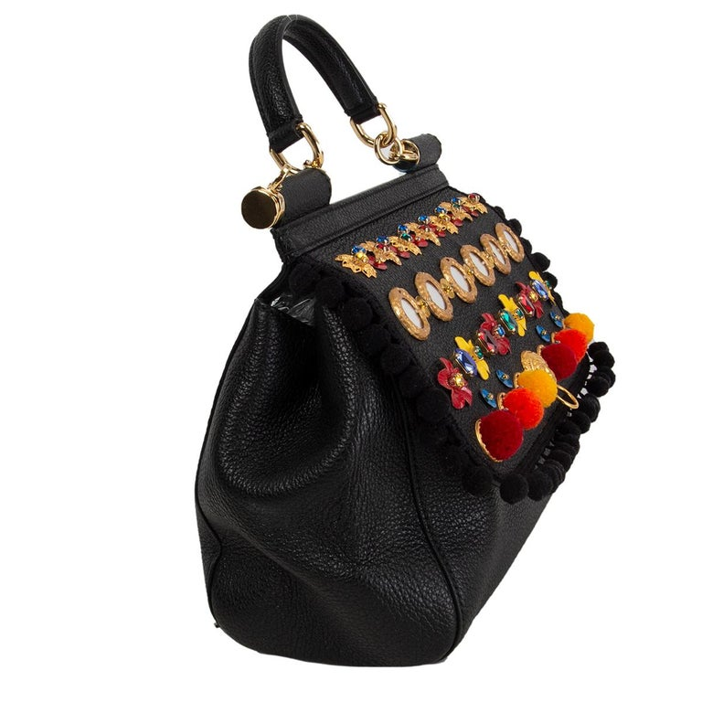Dolce & Gabbana 'Medium Sicily' shoulder bag in black grained calfskin featuring emblems, crystals, flowers, majolica ceramic, lion head and pom-pom embellishments arounf the trim. Opens with with two magnetic buttons under the flap and ins lined in