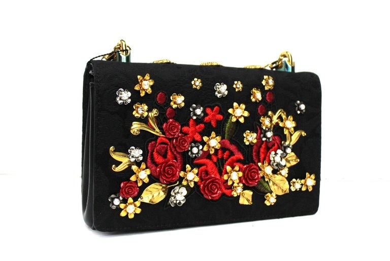 Very special Girls by D&G in black leather and fabric with sewn roses and metal appliqués. The hardware is gilded, with magnetic button closure, internally capacious for the essentials. Removable shoulder strap to wear it however you