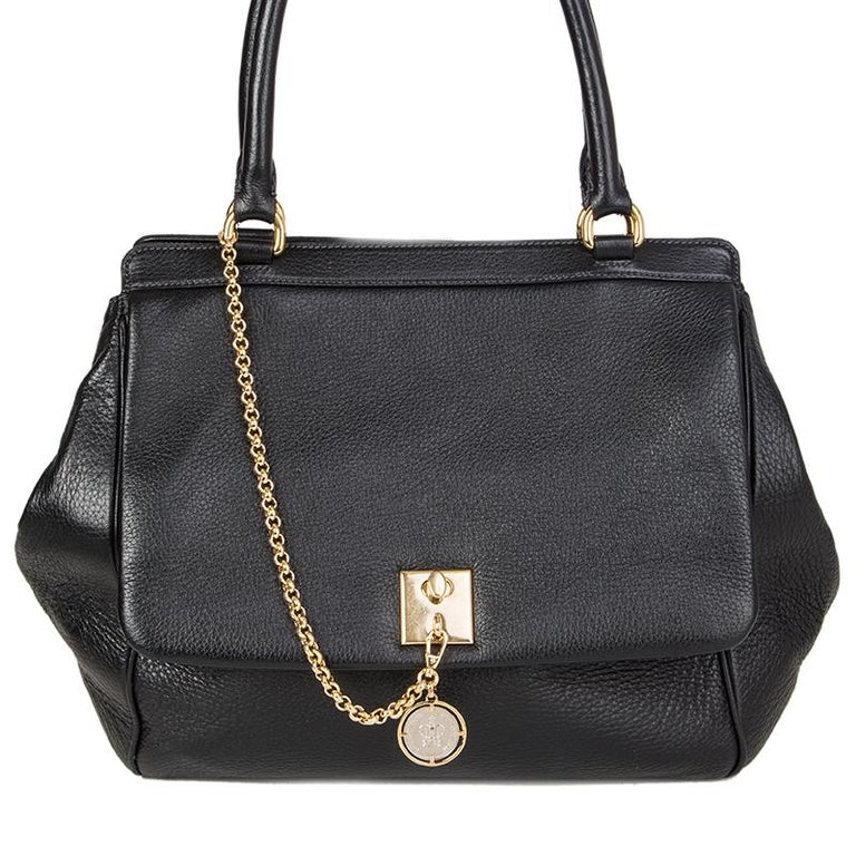Dolce & Gabbana large shoulder bag in black grained leather. Flap pocket with lock and crown-coin. Closes with a magnetic-snap on top. Lined in leopard fabric with two open pockets against the front and a zipper pocket against the back. Has been