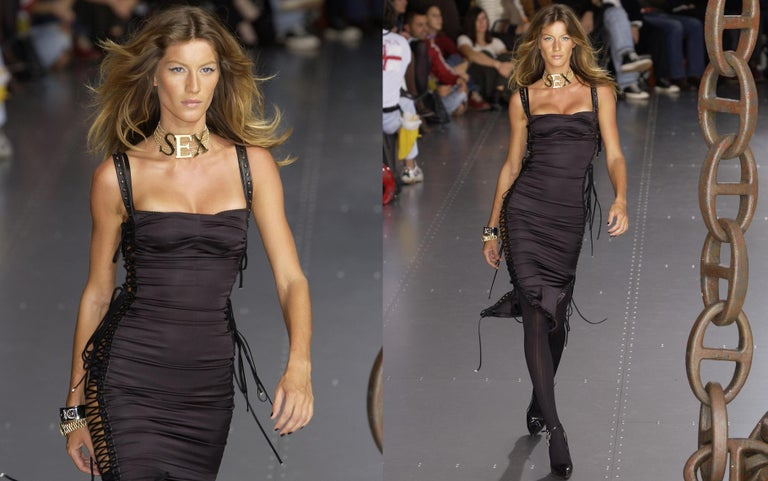 Dolce & Gabbana; black silk spandex figure hugging evening dress.     - Lambskin leather grommet trim   - Open on both sides with lace up fastenings  - Invisible side zip closure     Spring-Summer 2003    *due to the lace up fastenings the dress can