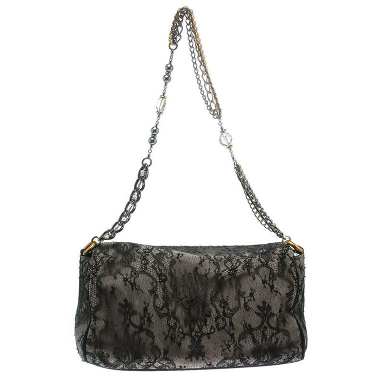 Stylish and handy, Miss Charles shoulder bag from Dolce and Gabbana is crafted from black/taupe lace and suede. The bag comes with a chain link handle and a spacious suede and fabric lined interior that houses a zip pocket. Sophisticated and stylish