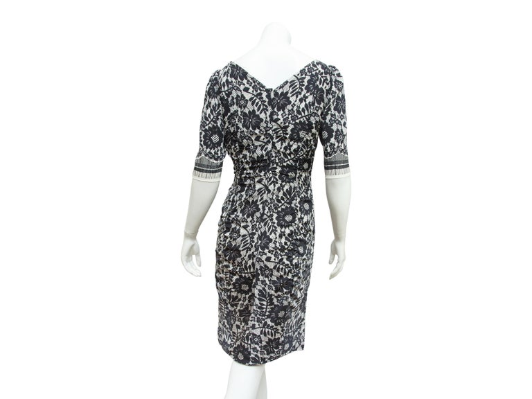 Product details:  Black and white lace-printed dress by Dolce & Gabbana.  Deep scoopneck.  Elbow-length sleeves.  Ruched bodice.  Concealed back zip closure.  32