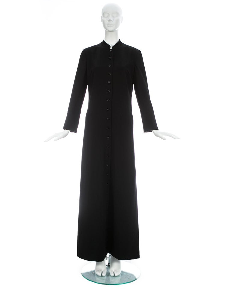 Dolce & Gabbana; Black wool full length priest coat with 23 button closures, 2 hidden side pockets, and red silk lining  Fall-Winter 1997