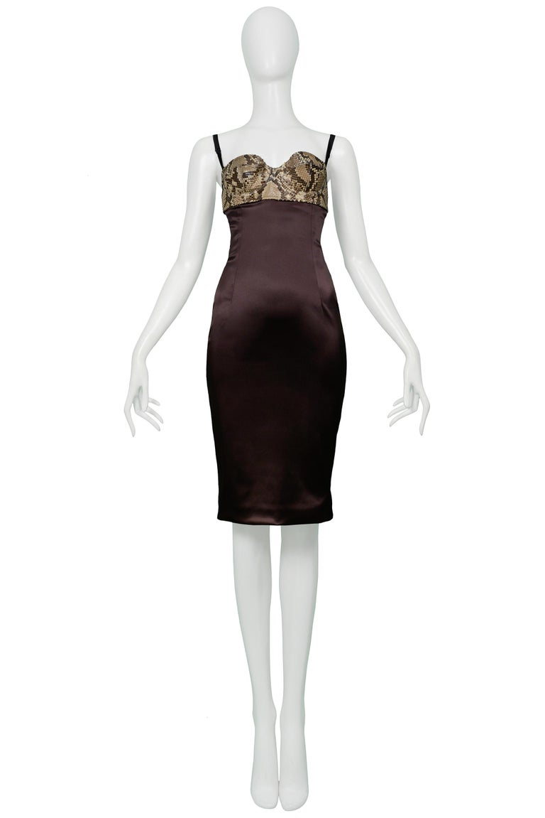 Resurrection is excited to offer a vintage Dolce & Gabbana brown satin cocktail dress featuring a snake print python leather bra top, adjustable straps, hook and eye closure, and center back zipper.   Dolce & Gabbana  Size 40 Python, Acetate, Nylon