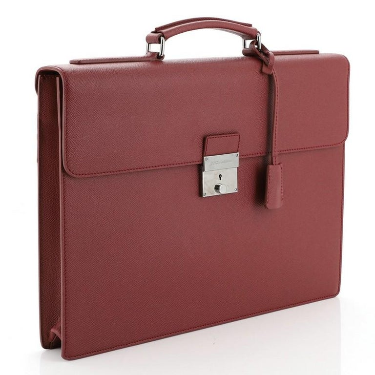 This Dolce & Gabbana Dauphine Briefcase Leather, crafted in red leather, features a leather top handle, foldover top with push-lock closure, exterior back pocket and gunmetal-tone hardware accents. Its push-lock closure opens to a black fabric