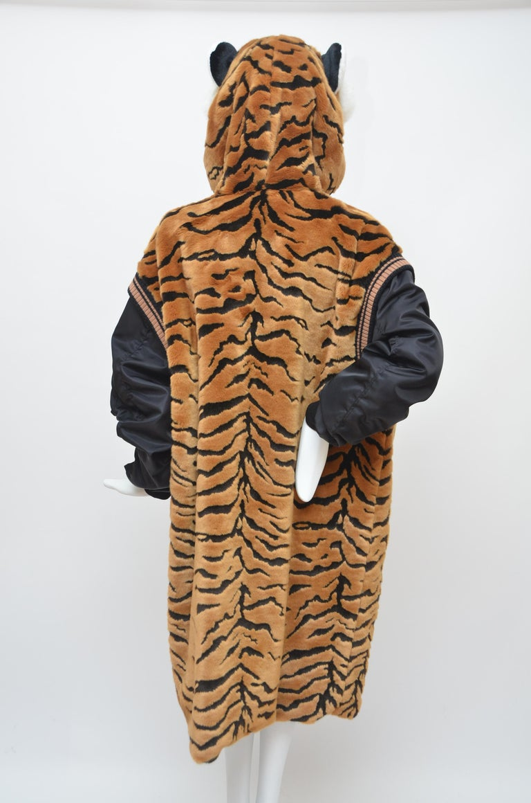 Dolce & Gabbana brown faux fur tiger hooded jacket features a hood, a front zip fastening, a faux fur trim, ribbed trimming, long sleeves, zipped pocket at the sleeve and ribbed cuffs. Fabris contents:Outer: Acrylic 76%, Polyester 14%, Polyamide