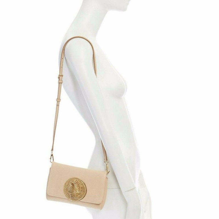 DOLCE GABBANA gold roman coin flap front tan leather clutch crossbody small bag  DOLCE & GABBANA Tan pebble leather upper. Gold-tone roman coin detail at front face. Flap front. Magnetic button closure. Gold-tone D-ring with clasp hook. Removable