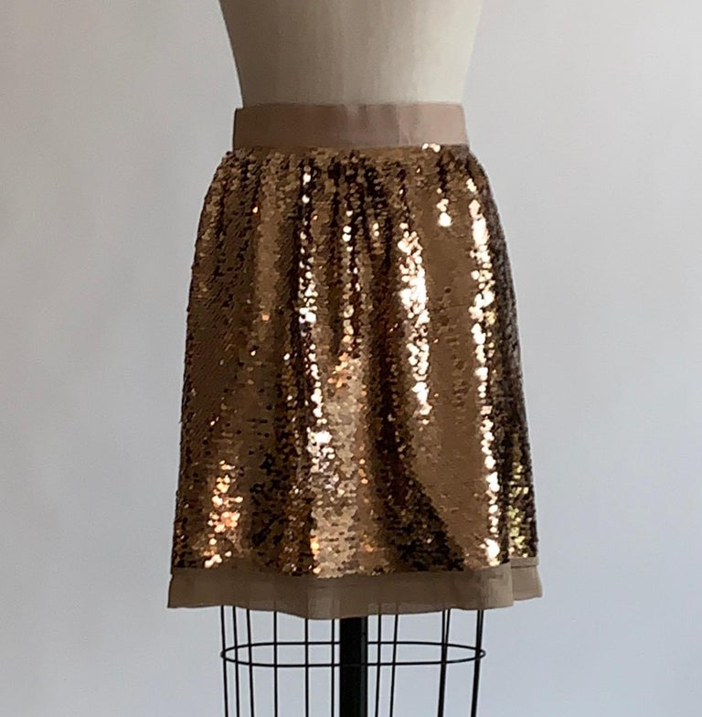 Dolce & Gabbana gold sequin skirt with beige silk trim and a grosgrain band at waist. Back zip inscribed with Dolce & Gabbana and  zipper pull with dangling D and G.    Outer: 100% polyester mesh (covered in sequins.)  Fully lined in 100% silk.
