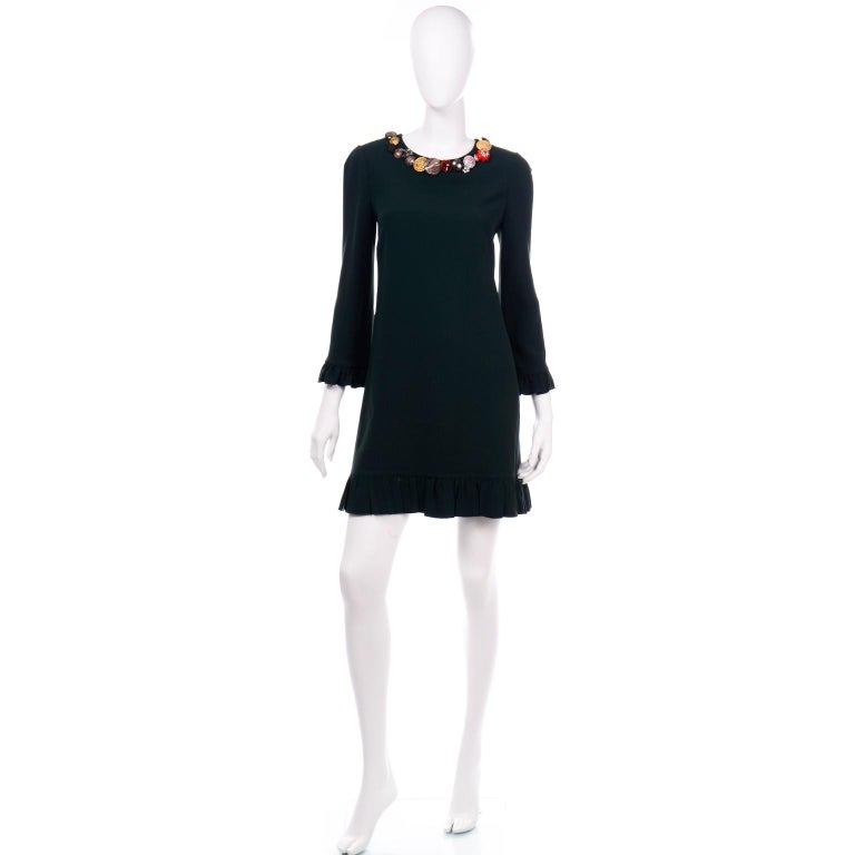 This Dolce & Gabbana dress is in a beautiful deep forest green with lovely ruffle trim on the 3/4 length sleeves and the hem. The collar of this dress is why we fell in love with it! It is embellished with assorted buttons (including some Dolce &
