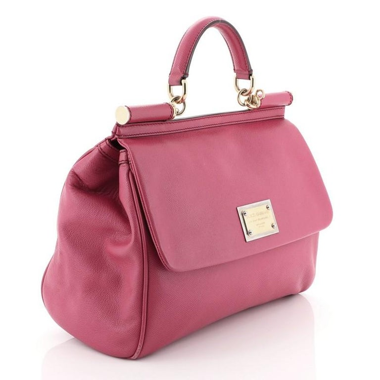 This Dolce & Gabbana Miss Sicily Bag Leather Large, crafted in pink leather, features a leather top handle and gold-tone hardware. Its framed top flap with magnetic snap closure opens to a brown printed fabric interior with zip and slip pockets.