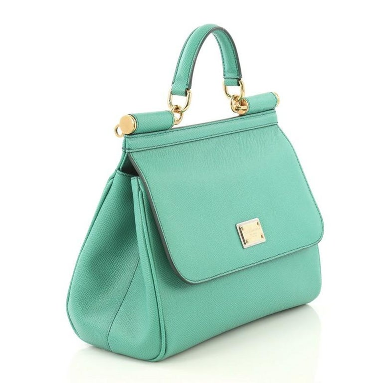 This Dolce & Gabbana Miss Sicily Bag Leather Medium, crafted in green leather, features a leather top handle, protective base studs, and gold-tone hardware. Its framed top flap with magnetic snap closure opens to a printed fabric interior with zip